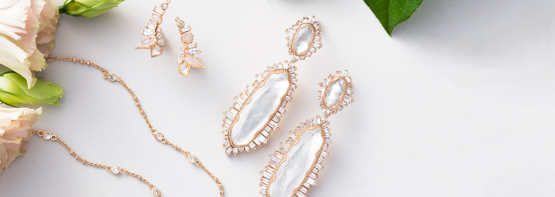 Kendra Scott Bridal Collection Rose Gold earrings and necklace with boquet on white surface